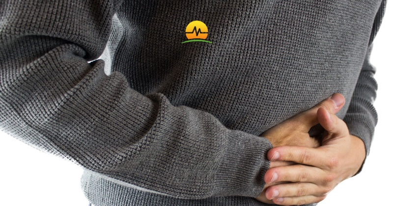 Man in gray sweater holds pressure against lower abdominal hernia may need hernia repair. Memorial Advanced Surgery logo at top center.