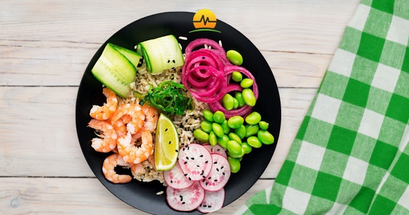 Colorful bowl of shrimp, cucumbers, pickled onions, radish, edamame, and brown rice demonstrate eating for weight loss and health is not boring with Memorial Advanced Surgery logo at top center.