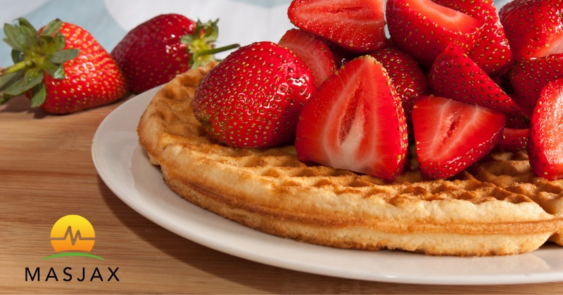 Waffle on white plate topped with sliced fresh strawberries. MasJax logo in the bottom left corner.